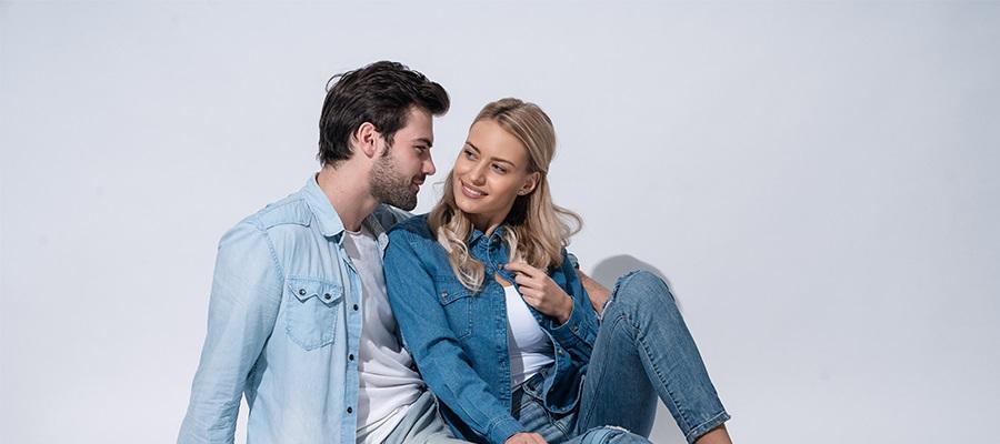 Lächelndes Paar trägt Jeansoutfits
